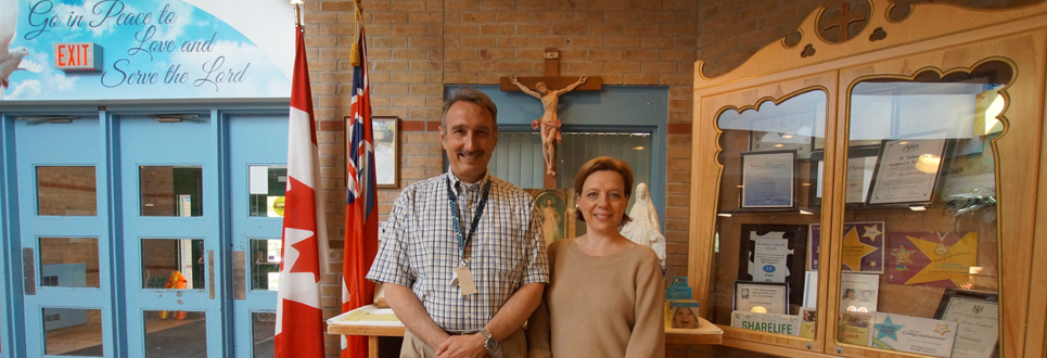 Male adult and female adult standing in front of school alter