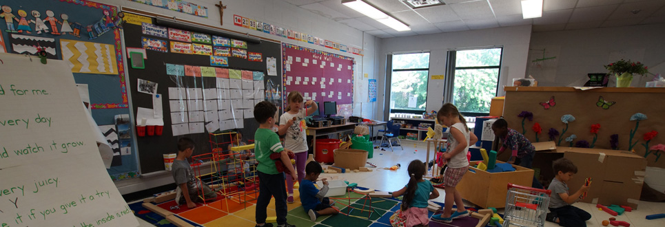 Students playing in a classroom filled with various toys and activities